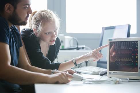 Zwei Studierende an einem Monitor